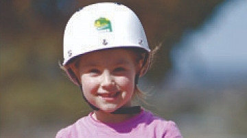 A young girl in a pink top wears a white riding helmet and is smiling broadly.