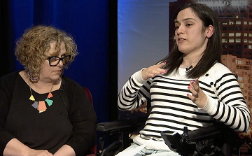 A woman and a younger disabled woman talk in a TV studio.