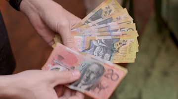 A close up on a woman's hands fanning out a bundle of $50 and $20 notes of cash.