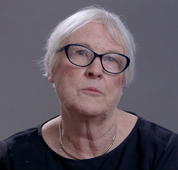 A woman with grey hair and glasses is seen against a grey background.