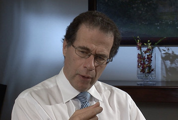 Bruce Bonyhady talks thoughtfully.  he is wearing a white shirt with a blue and white striped tie.  Art and a vase of flowers are visible in the background.