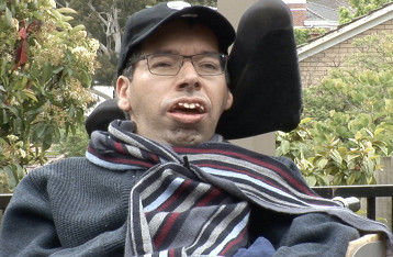 Dr George Taleporos sits outdoors in his wheelchair wearing a striped scarf and a peaked cap.