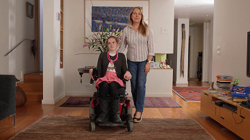 In a smart living room a teenage girl sits looking serious in her electric wheelchair while her mother stands at her side with her hand on the back of her chair.