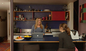 A woman stands in a kitchen with a lap top computer open in front of her.  Her daughter sits opposite her.